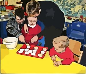 A boy sits with a cupcake baking try in front of him. Two adults cooperate around him to put cake mixture into the tray.
