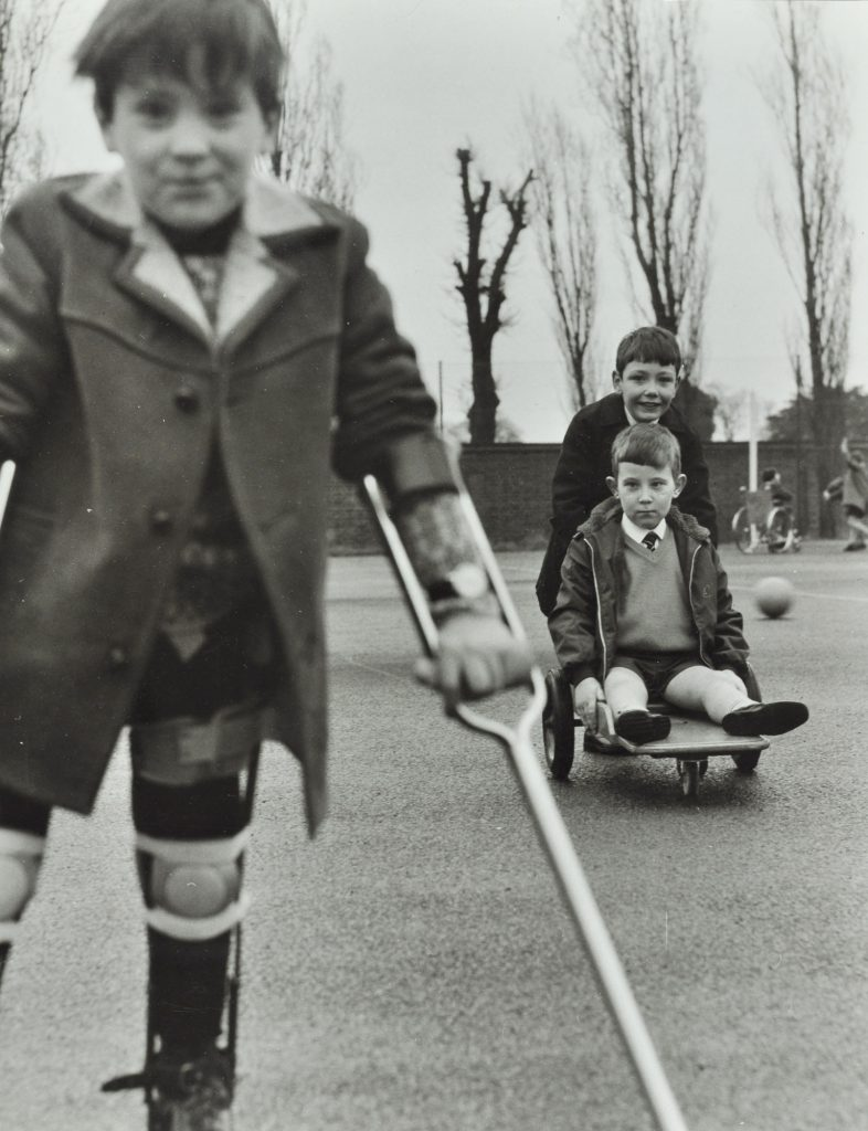 Child with crutch in old black and white photo