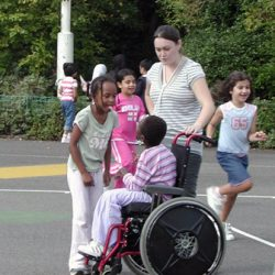 Playground scene with boy in wheelchair, girl sticking her tongue out at him, and a supervisor.