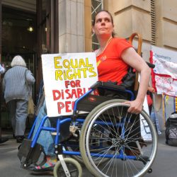 A DPAC wheelchair user at the Dept for Education holds a placard on her lap which reads