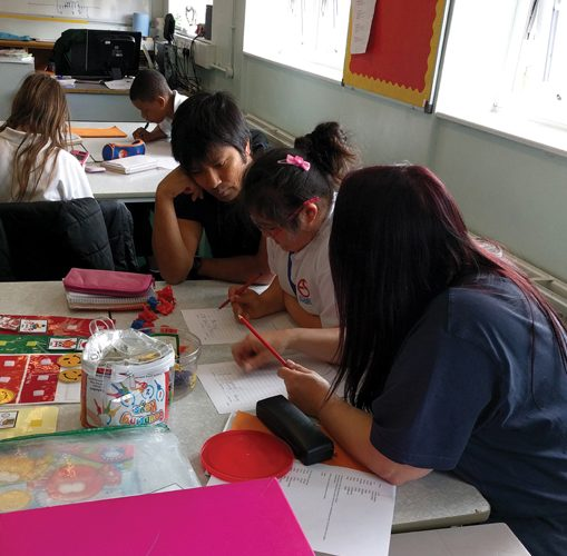 Teacher, child and teaching assistant in classroom sitting together looking at work