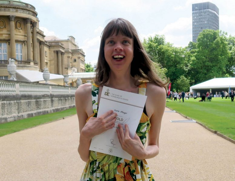 cover of Inclusion Now 48: a young disabled woman clutches her Duke of Edinburgh award certificate outside Buckingham Palace and smiles towards the sky