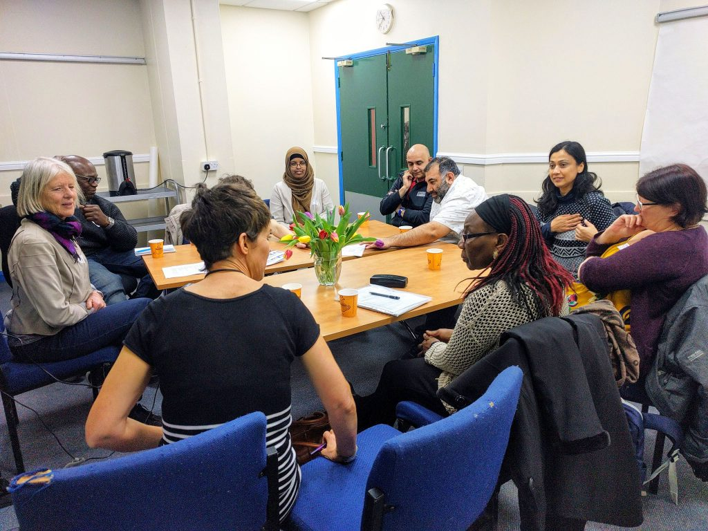 Ten people round a table talking in a workshop