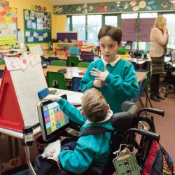 Two boys talking in a classroom, one in a wheelchair, one standing
