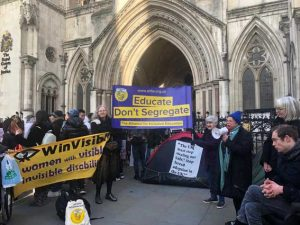 """Protestors outside the High Court holding up an ALLFIE banner saying """"Educate Don't Segregate"""", with other protestors holding up a banner saying """"WinVisible, Women with visible and invisible disabilities"""""""