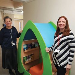 Emma Murray and Tara Welch with oval reading booth containing a comfy seat and bookshelf
