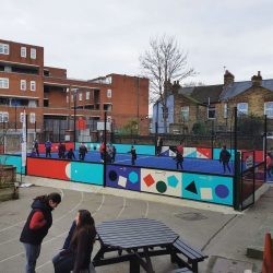 The school playground containing the new astroturf pitch, with girls and boys playing football on it