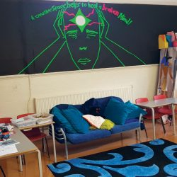 """The room known as the Engine Room, containing a blue comfy sofa and rug, colouring things, and a board saying """"a creative space helps to heal a broken mind"""""""