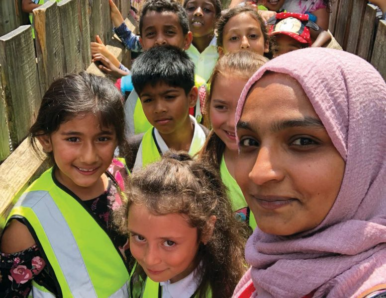 A group of students and staff from Seven Sisters school crowding in and smiling at the camera