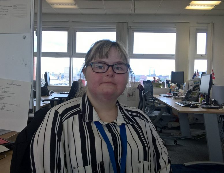 Katie in her office wearing a stripy shirt, looking at the camera with desks and windows behind