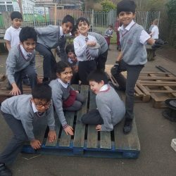 a group of children in uniform playing on a seesaw made of pallets