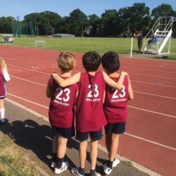 Three small boys with their arms round each other on an athletics track, backs to the camera
