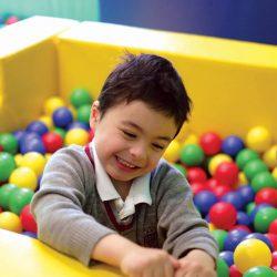 small boy in ballpit, wearing school uniform