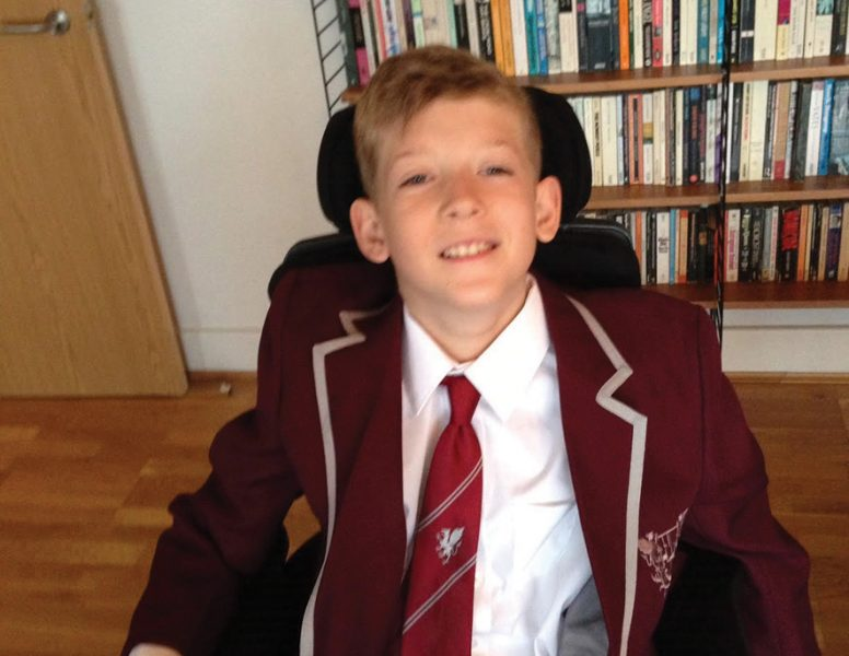 Ethan on his first day at secondary school - sitting in a wheelchair smiling