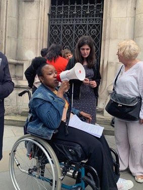 Yewande from ALLFIE speaking through a loudspeaker. Yewande is a wheelchair user.