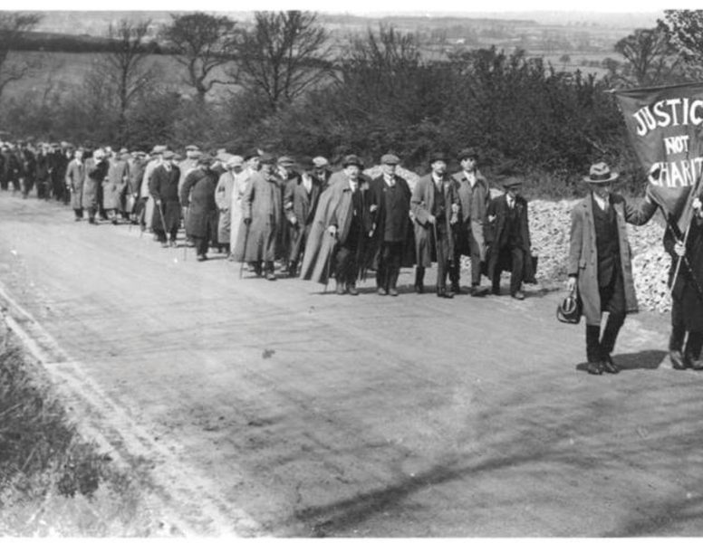Old black and white photo of a long line of marchers winding through the countryside