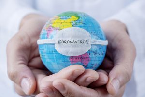 Doctor holding in hands a world globe with the word coronavirus