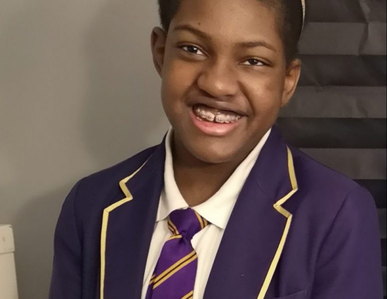 Head and shoulders shot of Kadijah Adam at school. Kadijah is a Young Black woman with her hair tied back and she is pictured in her St Paul's Catholic School uniform, which is purple and yellow.