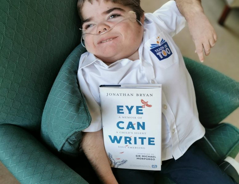 Jonathan Bryan, a Disabled Young campaigner and author is pictured with his book, 'Eye Can Write'. He is a Young white man wearing a shirt with the logo of his charity, 'Teach Us Too', on it.