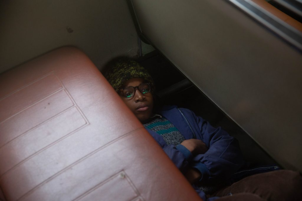 Still from the BBC film, 'Small Axe: Education' by director Steve McQueen, depicting the main character, Kingsley, hiding under the seat of the school bus. Episode: Education. Shows: Kingsley Smith (Kenyah Sandy) / Copyright: BBC/McQueen Limited.