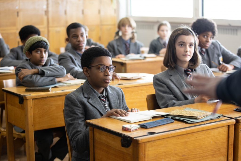 Scene from the BBC film, 'Small Axe: Education' by director Steve McQueen, depicting characters sat at desks in a school classroom setting, with main character Kingsley centre of shot. Education, from the Small Axe season, stars Kenyah Sandy as 12-year-old Kingsley, Ryan Masher as Joseph and Nigel Boyle as Mr Hamley. Copyright: BBC/McQueen Limited.