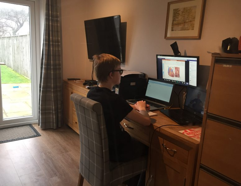 Young campaigner for Deaf and Disabled people's rights, Daniel Jillings, sat at his home computer, doing his school work remotely during the COVID-19 lockdown.